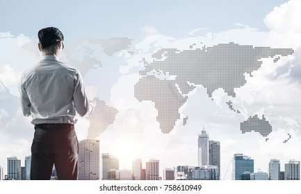 Young elegant businessman standing with back looking at business city