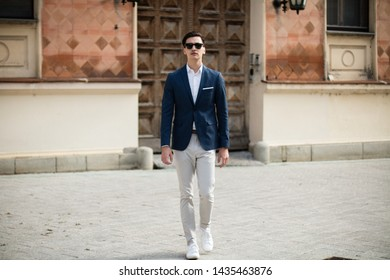 Young elegant businessman walking on the street.