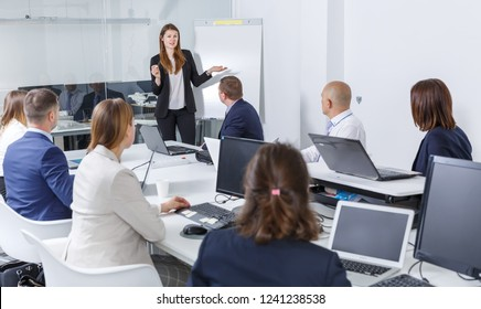Young elegant businesswoman making presentation to colleagues in modern meeting room