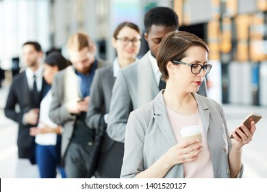 Young elegant businesswoman reading message in smartphone and having coffee while standing in queue to registration counter
