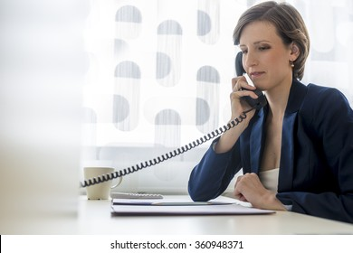 Young elegant businesswoman sitting at her office desk making a telephone call using white landline phone with paperwork or document in a folder in front of her.