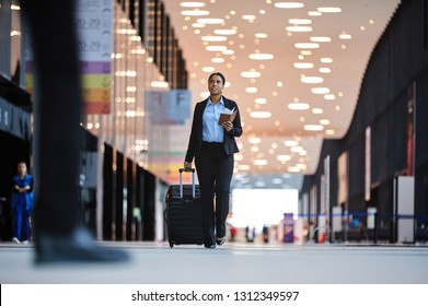 Young elegant businesswoman with suitcase and tickets walking along aisle in airport while hurrying for airplane