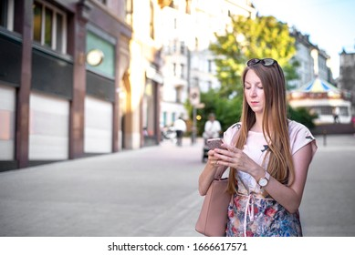 Young elegant caucasian woman looking serious while checking her cell phone or using a phone app in the street. Long hair, freckles