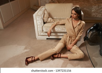 Young elegant caucasian woman with makeup, straight brown hair in beige overall sitting on floor in luxury apartmants leaning on armchair. Fashion style portrait