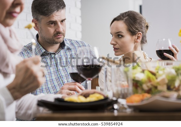 Young elegant couple arguing during sunday family dinner