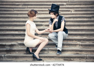 Young elegant couple on a stone stairs.