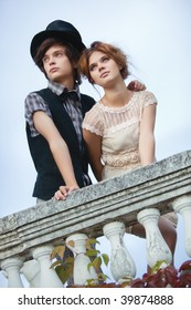 Young elegant couple standing at the railing.