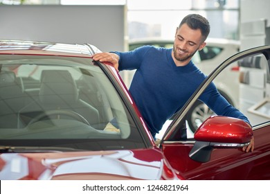 Young elegant driver sitting in his new red auto. Brunette client with beard in car salon testing red car before buying. Happy man in blue sweater smiling and standing near opened car's door.