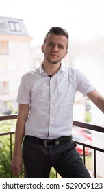 young elegant fashion man standing at balcony with arms crossed and smiling
