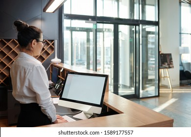 Young elegant female receptionist standing in front of computer screen by counter and waiting for guests in hotel