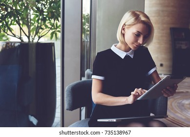 Young elegant female skilled managing director is reading e-mail on digital tablet positive feedback from the client about her work, while is sitting in luxury restaurant interior during break at job