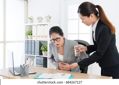 young elegant female staff knowing company manager getting stomach ache painful problem and prepared medical pills to care her.