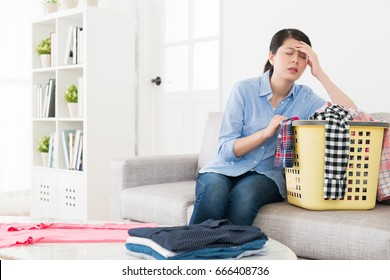 young elegant housewife making housekeeping feeling tired and getting headache painful when she folding clothing in living room.