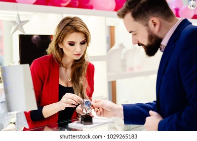 Young elegant man buying wrist watch in jewelry store. Customer service in jewelry store