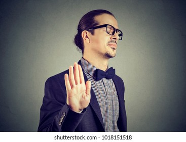 Young elegant man in eyeglasses stopping with hand while looking annoyed and insulted.
