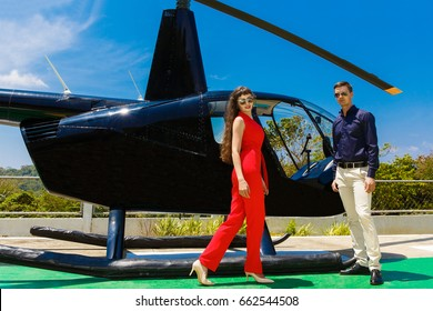 Young elegant man in sunglasses and a woman in red standing next to a private helicopter.