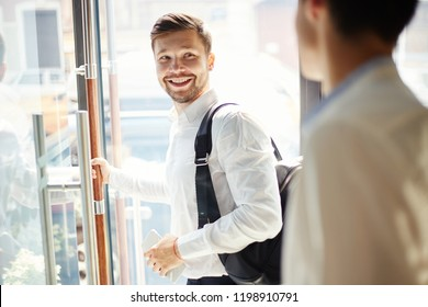 Young elegant man with trendy backpack walking out of cafe door and smiling over back saying goodbye