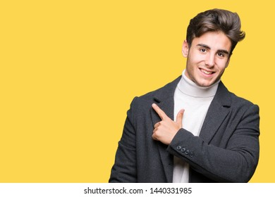 Young elegant man wearing winter coat over isolated background cheerful with a smile of face pointing with hand and finger up to the side with happy and natural expression on face