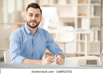 Young elegant office manager or consultant sitting in office in front of camera ready to answer your questions