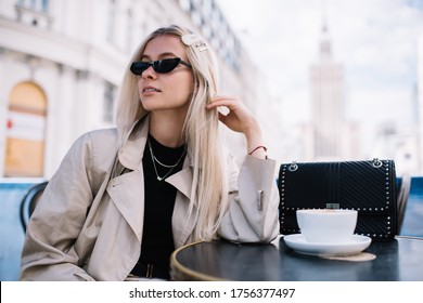 Young elegant socialite with blond hair in sunglasses sitting with cup of hot drink in outdoor cafe in sunny day