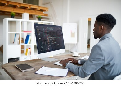 Young elegant software developer in formalwear sitting by desk in front of computer screen while decoding data