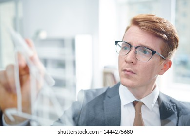 Young elegant student in suit and eyeglasses looking at transparent board