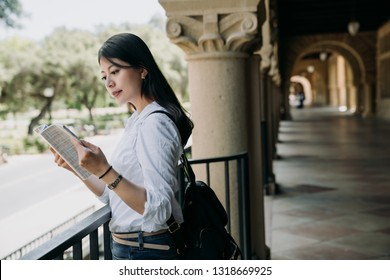 young elegant student woman reading textbook outside classroom at school studying. college girl standing indoor in hallway of old university building background in stanford. asian lady hard working.