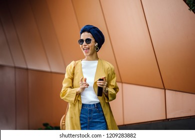A young, elegant and stylish Middle Eastern listens to music on hear wireless earphones that is streaming from her smartphone. She is wearing a turban (hijab, head scarf) and is dancing.