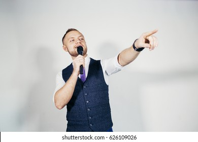 Young elegant talking man holding microphone talking with pointing finger. Isolated on grey background.