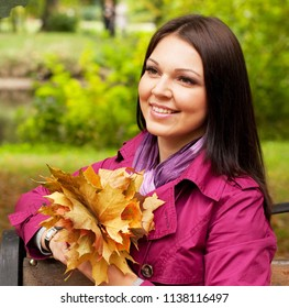 Young elegant woman with autumn leaves sitting on bench