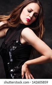 young elegant woman in black dress studio shot