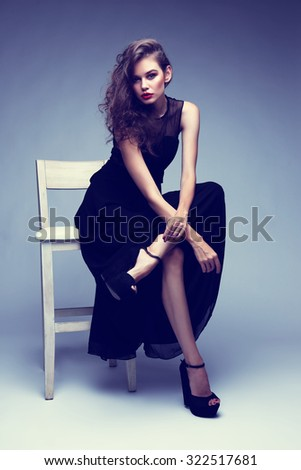 d33e96eaf Young elegant woman in black long dress, shoes. Sitting and posing in  studio. Curly hair, bright makeup. High fashion shot. - Image