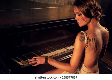 Young elegant woman in dress playing piano in retro style interior.