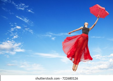 Young Elegant Woman Flying in the Sunny Blue Sky in the Black Gymnastics Leotard , Red Long Skirt with Red Polka Dot Umbrella