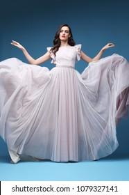 Young elegant woman in long pink dress. Elegant flying fabric, evening, wedding dress.