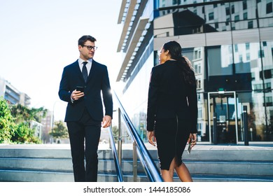 Young elegant woman and man in suits walking opposite on street stairway looking at each other against bright back lit