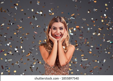 Young elegant woman in party and celebration mood isolated grey with confetti.