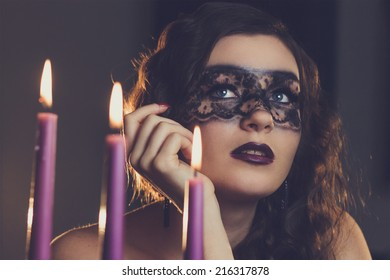 young elegant woman sitting near candles with make-up mask