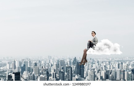 Young elegant woman with suitcase in hands siting on cloud