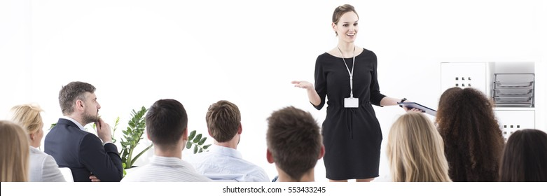 Young elegant woman as team lider presenting during corporation meeting