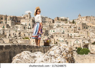 Young elegant woman tourist in historical Matera town in Italy standing on a wall looking at city landscape