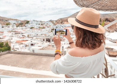 Young elegant woman tourist taking photos of ancient white town with her smartphone