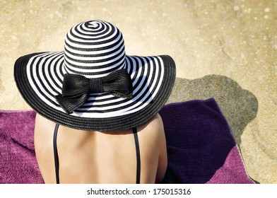 Young elegant woman wearing a black bikini top and a black and white striped beach hat sunbathing on the beach.