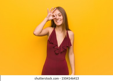 Young elegant woman wearing a dress confident doing ok gesture on eye