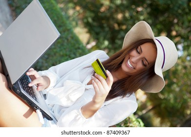 Young elegant woman wearing straw hat and white dress holding credit card with laptop sitting on bench at park and looking away. She is shopping or making payments carefree online