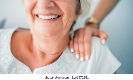 Young elegant woman's hand on senior lady's shoulder. Portrait of a smiling old lady with her nurse's hands on her shoulders. Sign of caring for seniors. Helping hands. Care for the elderly concept.