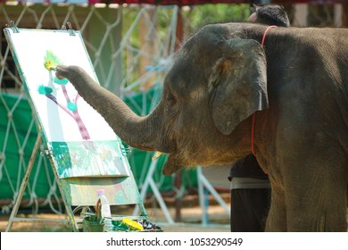 Young elephant drawing a picture of a tree with color paint