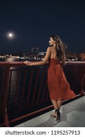 Young ellegant woman standing on the ligths of the night city background on bridge. Sexy romantic beautiful young mixed race Caucasian Asian girl with perfect makeup in long red evening dress standing