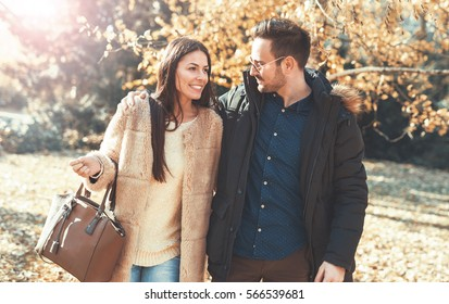 Young embracing loving couple walking through autumn park. Moments of happiness and joy, love and tenderness. Relationships, lifestyle concept