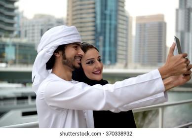 Young Emirati couple taking photos or selfie, Dubai, UAE
